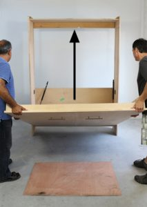 raising the wall bed frame into cabinet