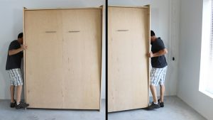 person moving the murphy bed cabinet against wall