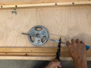 preparing the steel strapping for securing the weights to wall bed frame