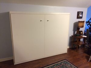 closed white wall bed made out of particle board