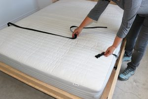 Undoing mattress strap on Queen-size wall bed