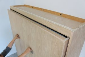 Opening wall bed for removal of cabinet top stopper component