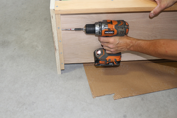 Removing screws from cabinet top component on wall bed